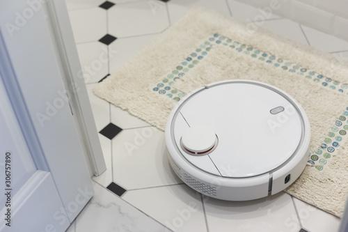 Fototapeta White robot vacuum cleaner on carpet in bathroom obraz na płótnie