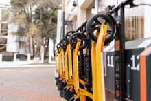 The Eco-vehicles. Orange Electric Scooter In A Row Located At The City Transport Rental Counter. Outdoor, Street. Horizontal Orientation