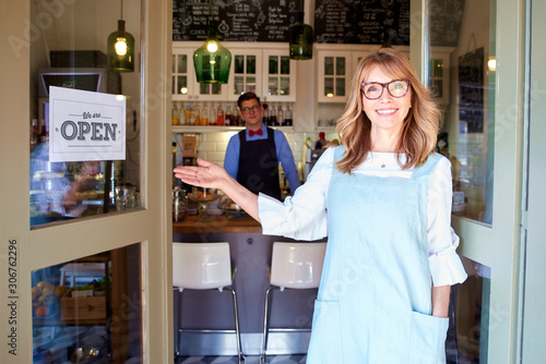 Foto Small business owner woman standing in cafe door and smiling