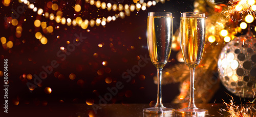 Foto auf Leinwand Alkohol Holiday Champagne Flute over Golden glowing background. Christmas and New Year celebration. Two Flutes with Sparkling Wine over Holiday Bokeh Blinking Background. Table setting, decoration
