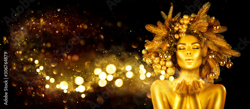 Fototapeta Christmas golden Woman. Winter girl pointing Hand, blowing blinking stars,  Beautiful New Year, Christmas Tree Holiday Hairstyle and gold skin Makeup. Gift. Girl in decorated Xmas wreath. Beauty Model obraz