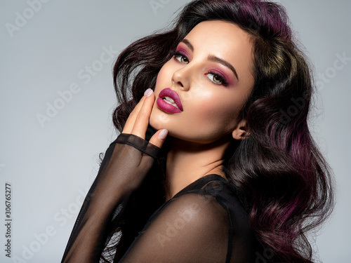 Foto  Portrait of beautiful young woman with bright maroon makeup
