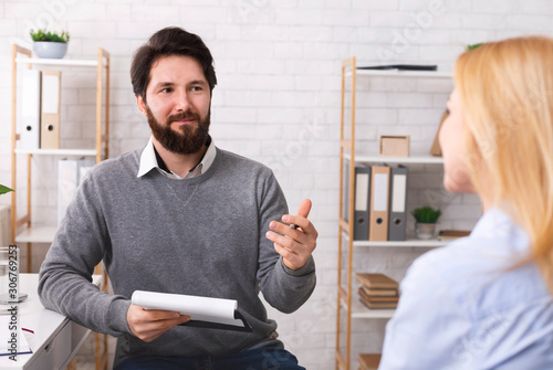 Friendly psychotherapist talking to young female patient