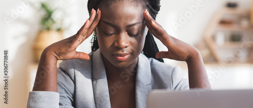Tired black businesswoman suffering from migraine at workplace in office Canvas Print