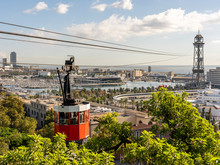 Historic Red Cable Car Cabin With Harbor And Panorama Of Barcelona City, Spain