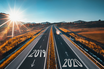 Driving on open road at beautiful sunny day to new year 2020. Aerial view