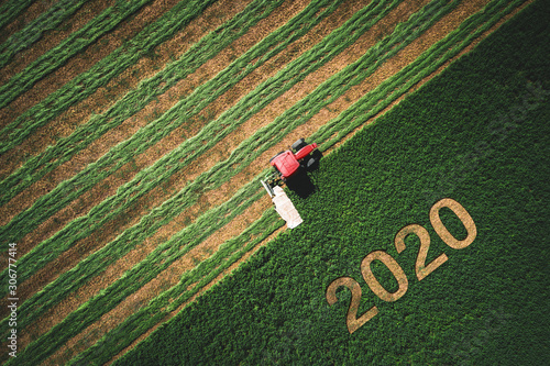 2020 Happy Ney Wear concept and red tractor mowing green field