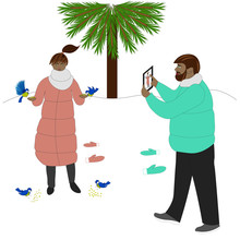 Young Couple Outdoor. Girl Is Feeding Birds Anp Man Is Making Her Photo.