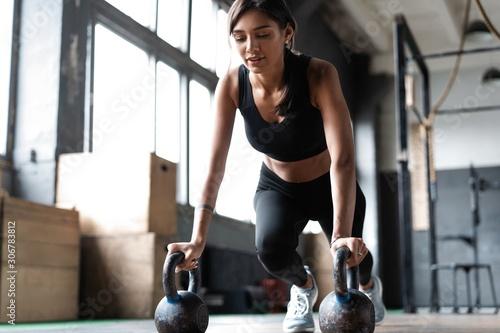 Fototapeta Slim brunette doing push-ups exercises on kettlebells. Cross fit training obraz