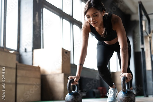 Obraz Slim brunette doing push-ups exercises on kettlebells. Cross fit training - fototapety do salonu