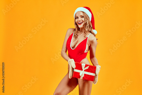Beautiful girl stands on a yellow background dressed in a swimsuit, gloves and hat of Santa Claus holding a gift smiling and looking at the camera. - 306783839