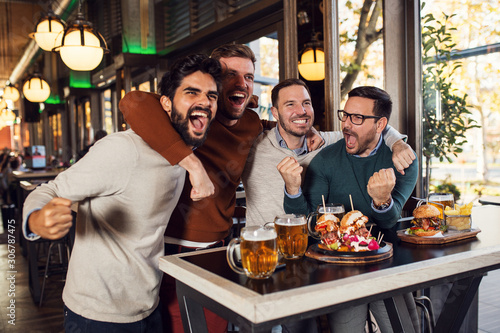 Excited group cheering for sport team in pub Canvas Print