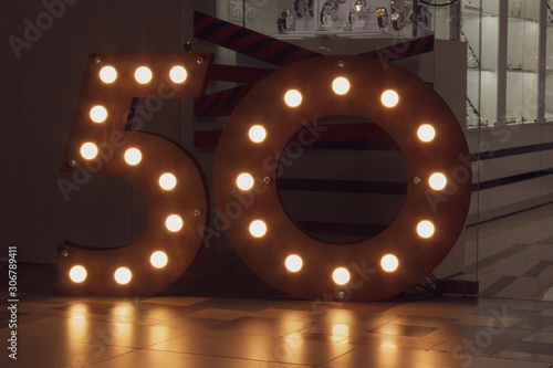 Fototapeta number 50 carved from wood with bright bulbs around the perimeter. The concept of discounts and sales in stores, an important date - anniversary, anniversary, birthday obraz na płótnie