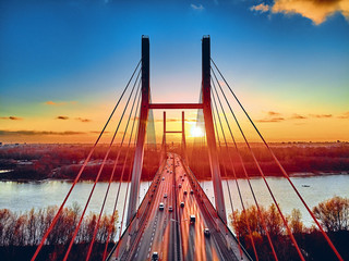 Fototapeta Mosty Beautiful panoramic aerial drone view to cable-stayed Siekierkowski Bridge over the Vistula river and Warsaw City skyscrapers, Poland in gold red autumn colors in November evening at sunset