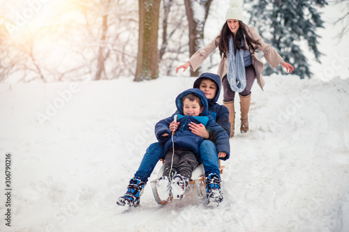 Obraz Young, beautiful mom and her cute little boy enyoing winter, sledding - fototapety do salonu