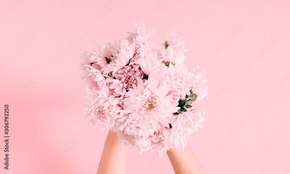 Fototapeta Beautiful flowers composition. Women's hand hold bouquet of pink light flowers on pastel pink background. Valentines Day, Mother's day. Flat lay, top view, copy space