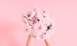 Beautiful flowers composition. Women's hand hold bouquet of pink light flowers on pastel pink background. Valentines Day, Mother's day. Flat lay, top view, copy space