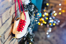 Pair Of White Vintage Leather Skates With Red Laces Hanging On Old Rustic Brick Wall With Blurred Lights On Christmas Tree Decoration. Cozy Scenic Christmas Card Interior Winter Holidays Background