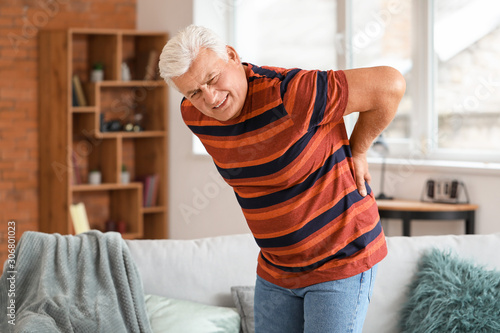 Cuadros en Lienzo Senior man suffering from back pain at home
