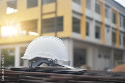 Fotografia  Hard hat safety on computer notebook building construction estate background