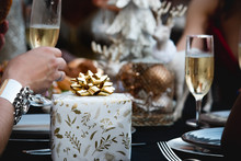 Glass Of Champagne In Restaurant With Christmas Gift On The Table Xmas Party