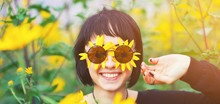 Close Up Creative Portrait Of A Beautiful Young Smiling Happy Brunette Girl With Yellow Flower Petals Under Sunglasses On Background Of A Field Of Sunflowers. Woman Summer Lifestyle And Healthy Teeth.