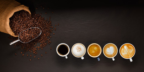 Variety of cups of coffee and coffee beans in burlap sack on black background.