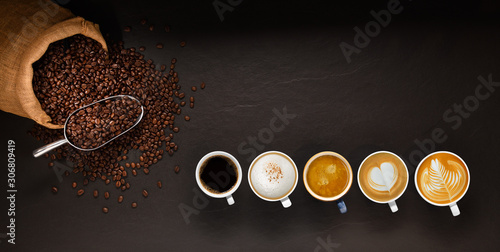 Slika na platnu Variety of cups of coffee and coffee beans in burlap sack on black background