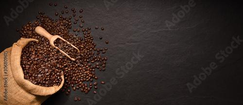 Fotobehang Koffiebonen Coffee beans in burlap sack on black background