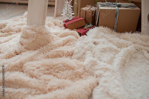 Obraz cozy fluffy plaid pastel shades on the background of gift boxes - fototapety do salonu