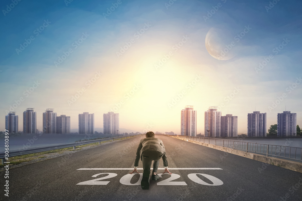 Fototapeta Asian business person ready to run new year 2020 toward the city. Business concept