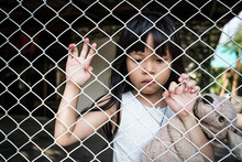 The Sad Asian Girl Child, While Sitting Alone In Cage Was Imprisoned Make No Freedom Or Lack Of Freedom