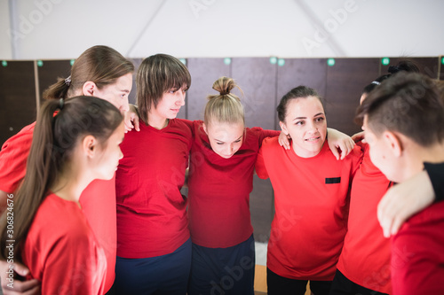 obraz PCV Large group of young sportswomen in red t-shirts standing in circle