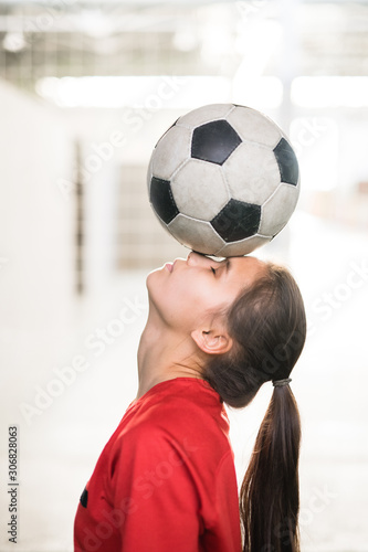 Fotografiet Young female football player in red t-shirt holding soccer ball on her face
