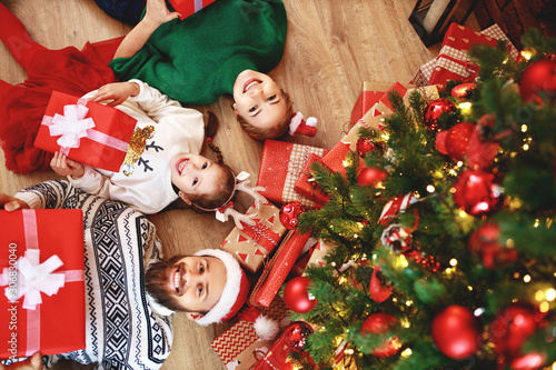 Spoed Foto op Canvas Wanddecoratie met eigen foto . happy family mother, father and child with gifts near Christmas tree at home.