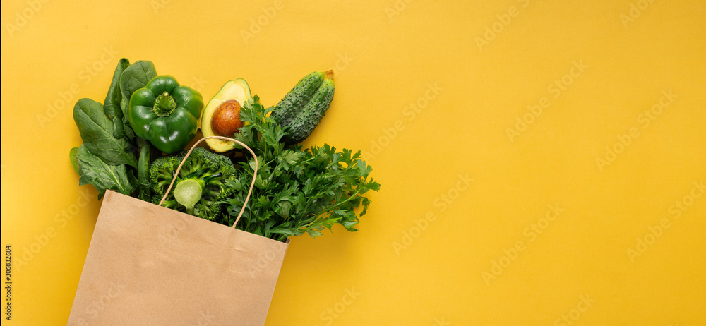Fototapeta Shopping bag full green vegetables on yellow background with copy space  Purchase healthy food concept