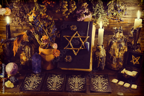 Creepy witch book with pentagram, tarot cards, runes, gemstone, candle and magic objects Canvas Print