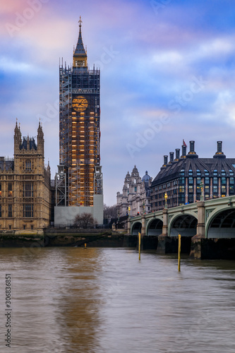 Big Ben covered in scaffolding for restoration and Portcullis House across Thames river before sunset in London, England
