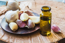 Garlic Oil In A Glass Bottle Near Ripe Garlic On A Background Of Blue Old Boards. C