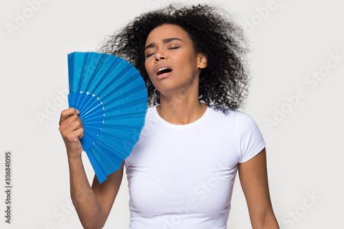 Fototapeta Tired African American woman suffering from heat, waving fan obraz