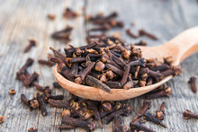 A Spice Of Dried Cloves Lies On A Wooden Spoon And Is Scattered On Old Wooden Boards.