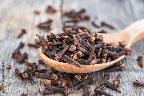 Foto A spice of dried cloves lies on a wooden spoon and is scattered on old wooden boards