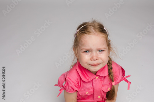 Fotografia Little girl in pink shirt looking aside and crying on isolated background