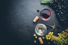 Glasses Of White And Red Wine With Ripe Grapes On Black Stone Background, Top View