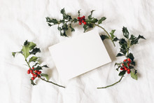 Christmas Styled Stock Photo. Festive Greeting Card, Invitation Mockup Scene. Still Life With Paper Card And Holly Berries On White Linen Background. Winter Stationery Composition. Flat Lay, Top View.