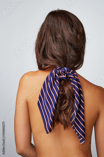 Close-up back shot of a brunette lady with a blue satin hair scarf fixed on the scrunchie with red and white stripes. The shirtless woman with a ponytail is posing on the gray background.  Wall mural