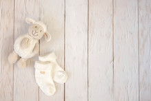Baby Socks And Toy Lamb On Light Wooden Background. Motherhood Concept. Top View, Flat Lay Composition. Copy Space For Text.
