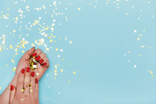 Woman Hands With Red Manicure On Blue Background With Golden Stars Sprinkles.