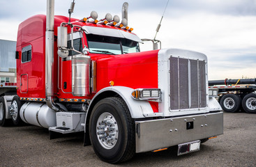 Classic big rig red semi truck tractor with chrome accessories and flat bed semi trailer standing on parking lot waiting for load