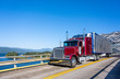 canvas print picture - Red classic bonnet big rig semi truck transporting frozen cargo in bright refrigerated semi trailer driving on the truss bridge across the river